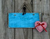 Blank blue wood sign with red heart with ribbon and iron keys hanging on rustic wooden background