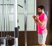 Standing biceps cable curl man in pulley machine workout at gym