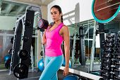brunette girl with dumbbell posing at gym after workout