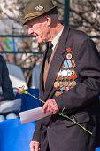 Elderly veteran of World War II near tribunes