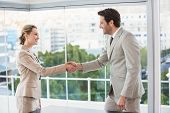 Two business workers shake hands in the office