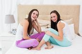 Pretty friends messing about on bed at home in the bedroom