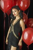 Beautiful exotic young woman wearing black dress with party balloon background