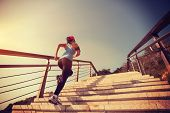 pic of stepping stones  - young woman runner running up on stone stairs sunrise seaside