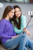 stock photo of two women taking cell phone  - Beautiful girls - JPG