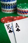 foto of poker hand  - A poker hand of ace king of clubs with chips in background - JPG