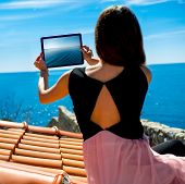 picture of sea-scape  - Young woman traveler photographing sea scape with digital tablet sitting on the roof of old building in Budva city - JPG