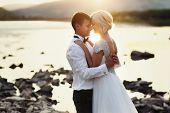 stock photo of bridal veil  - Wedding couple running on green grass at sunset - JPG