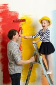 picture of fool  - Girl and father fooling while painting wall in bright colors - JPG