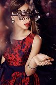 picture of face mask  - fashion photo of gorgeous woman with dark hair in elegant dress and mask on face posing in luxurious interior - JPG