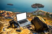 stock photo of knapsack  - Travel photographer equipment on rocky mountain with beautiful landscape on the background - JPG