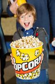 picture of exciting  - Portrait of excited boy offering popcorn bucket while father standing in background at cinema - JPG