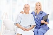 stock photo of hospital gown  - Young female doctor and a mature patient posing seated on a hospital bed - JPG