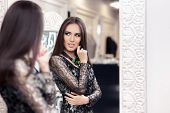 picture of evening gown  - Young woman in a dressing room with an evening gown and a statement necklace  looking in the mirror - JPG