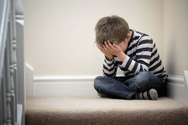 pic of headings  - Upset problem child with head in hands sitting on staircase concept for bullying - JPG