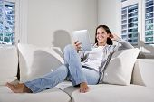 Hispanic Woman Reading Electronic Book On Couch