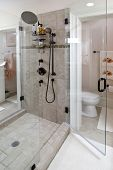 beautiful walk-through stone tile shower with dual shower heads