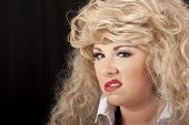 woman in blond wig and heavy makeup sneering