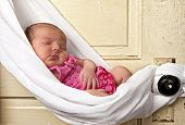 newborn baby sleeping in sling