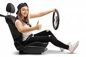 Teenage girl in a car seat holding a steering wheel and making a thumb up sign isolated on white bac poster