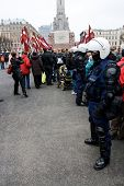 RIGA, LATVIA - MARCH 16: Local police guard the crowd at the Freedom Monument during Commemoration o