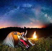 Night Tent Camping. Pair Sitting Near Tent And Campfire And Enjoying Incredibly Beautiful Starry Sky poster