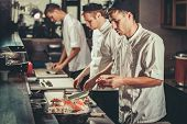 Food concept. Three young chefs in white uniform decorate ready dish in restaurant. They are working poster