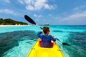 Back view of happy teenage boy on a kayak at tropical lagoon poster