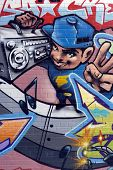 Detail of graffiti on an alley wall showing a young man holding a radio-cassette player.