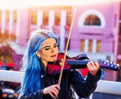Постер, плакат: Playing viola woman perform music on violin in park outdoor Girl with blue hairstyle and eyebrows p