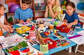 Small students girl and boy painting in art school class. Children drawing by paints on table. Male  poster