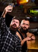 Man Bearded Hipster Hold Smartphone. Taking Selfie Concept. Send Selfie To Friends Social Networks.  poster
