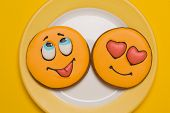 Two Yellow Cookies In The Shape Of Smiles Lie On A Yellow Plate, On A Yellow Background poster