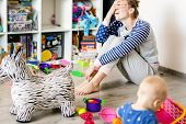 Tired Of Everyday Household Mother Sitting On Floor With Hands On Face. Kid Playing In Messy Room. S poster