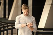 Man Athlete On Strict Face Checking Fitness Tracker, Urban Background. Athlete With Bristle With Fit poster