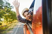 Image of happy woman 20s wearing straw hat laughing and waving hand out of the window while riding i poster
