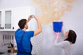 Woman Collecting Water In Blue Bucket From Damaged Ceiling While Repairman Taking Photograph On Mobi poster