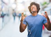 Afro american man over isolated background smiling crossing fingers with hope and eyes closed. Luck  poster