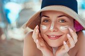 Skincare. Beauty Concept. Young Pretty Woman Applying Sun Cream  And Touch Own Face. Female In Hat S poster