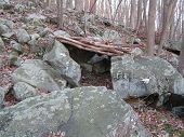 stock photo of fieldstone-wall  - man made shelter between large boulders on a steepe slope near a bike trail  - JPG