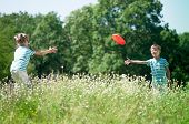 stock photo of frisbee  - Happy boy and little girl playing frisbee on a meadow in a sunny day