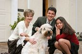 stock photo of young girls  - happy family with a dog in front of the home - JPG