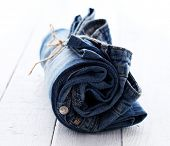Close up of jeans roll over wooden surface