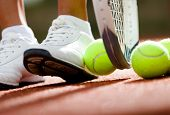 Legs of athletic girl near the tennis racket and balls