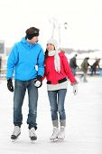 Romantic young couple in warm winter clothing holding hands and smiling at each other while ice skat