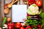 Vegetables and Spices on a Wooden Background and Paper for Notes.Open Notebook and Fresh Vegetables