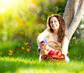 Happy Smiling Young Woman Eating Organic Apple in the Orchard.Basket of Apples. Harvest Concept.Gard