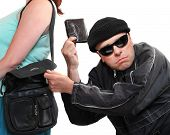 stock photo of stealing  - Thief stealing from handbag of a woman - JPG