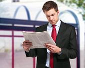 A businessman reads the finance newspaper while waiting for bus