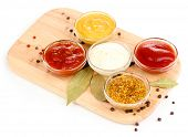 various sauces on chopping board isolated on white